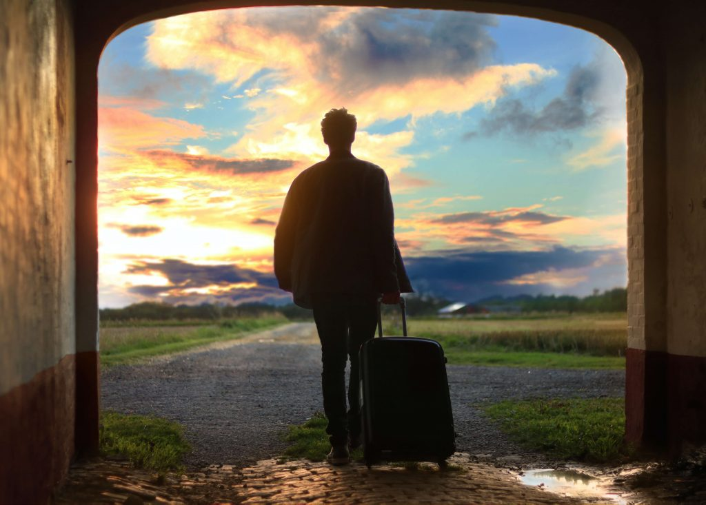 Person walking out into the sunset with suitcase in hand, person on a journey