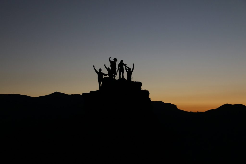 People standing at the top of a mountain celebrating