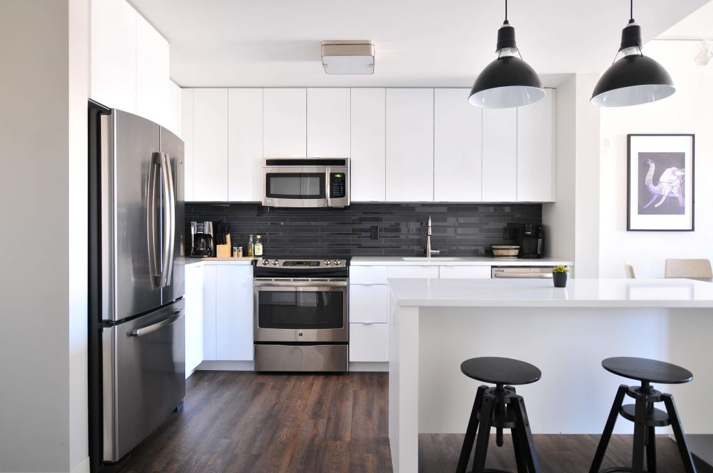 Inside of an apartment kitchen with black and white accents, group investing in an apartment property