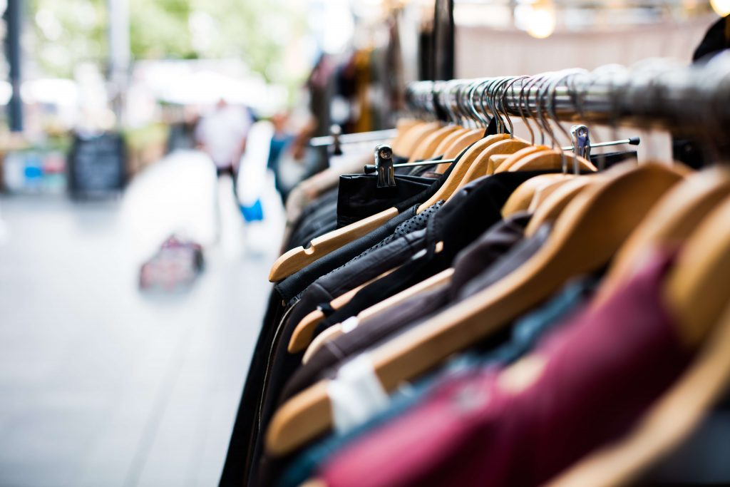 Clothes on a rack, retail shopping strip, group investing in commercial properties for passive income