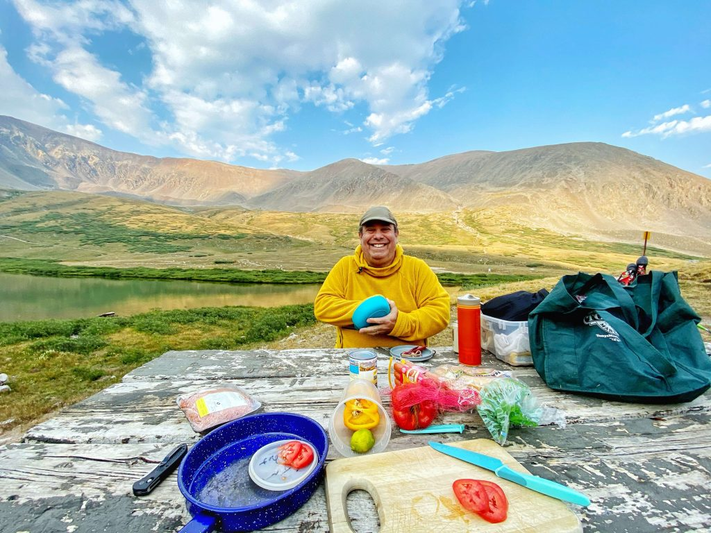 A person sitting in front of mountains eating a meal, how to create cash flow and residual income in order to re-gain your free time